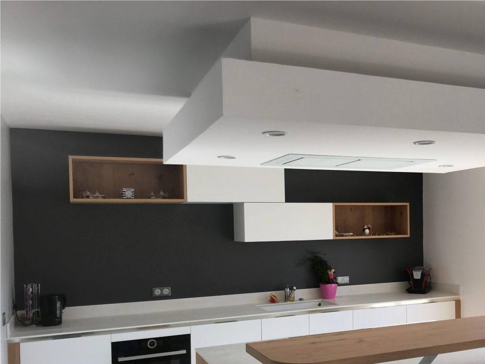 Réalisation d'une cuisine polymère blanc mat plan de travail céramique panneau bois chêne et hotte de plafond